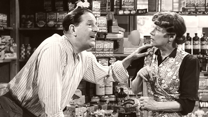 Kathleen Harrison (Lillian Lord) listens to shopkeeper Stanley Holloway (Henry Lord) in The Happy Family (1952)