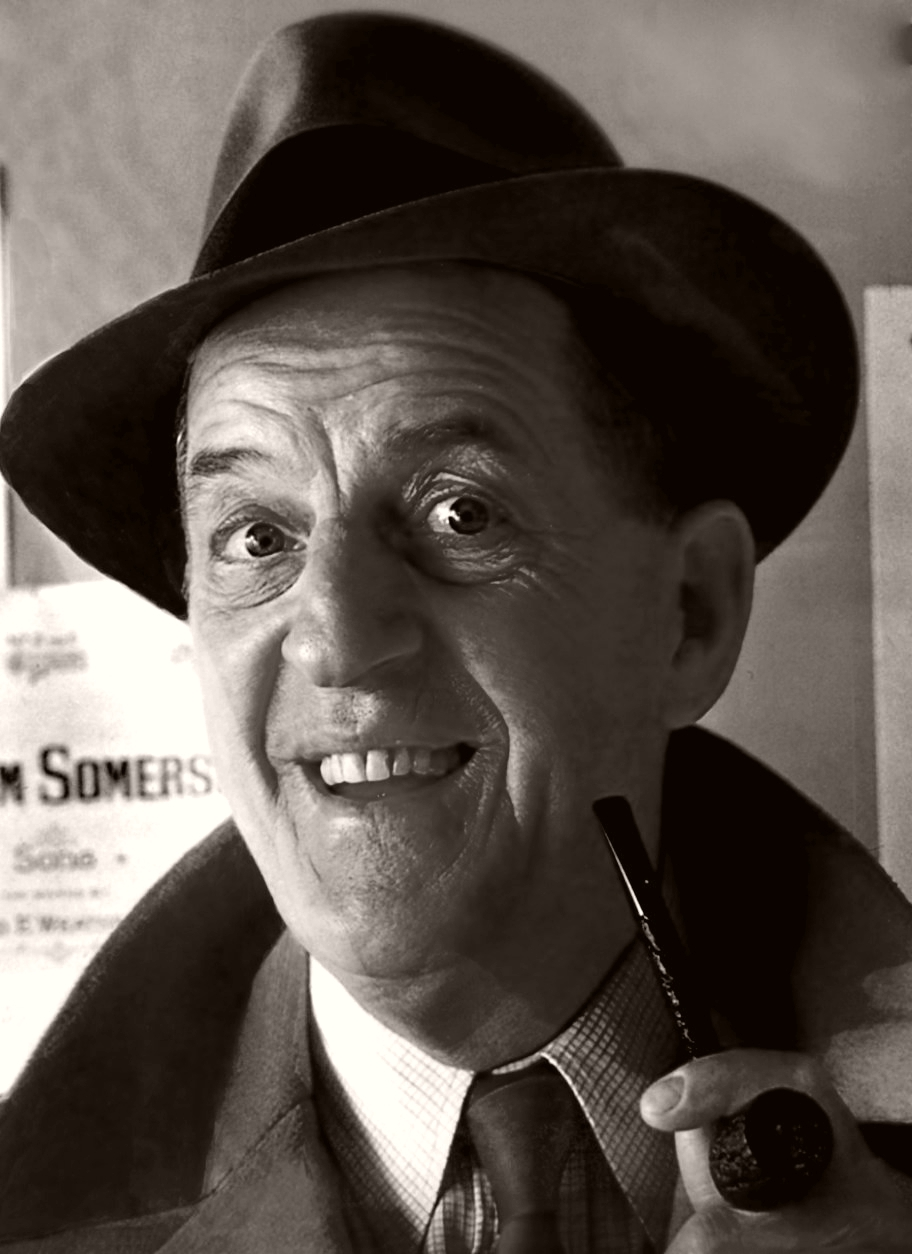 British comedian Stanley Holloway wears a trilby, jacket and tie as he smokes his pipe