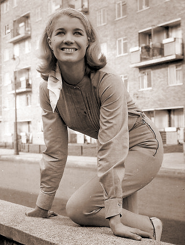 Julia Lockwood smiles in the street while outside a block of flats