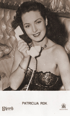 British actress Patricia Roc, dressed in evening wear, takes a phone call.  Beograd card featuring Patricija Rok.
