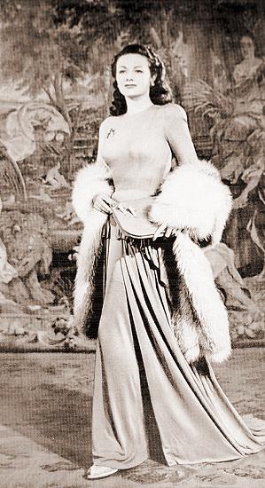Margaret Lockwood looks elegant on the carpet before a tapestry