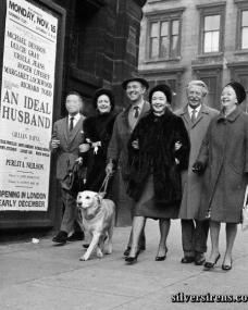 The cast from An Ideal Husband take the dog for a walk outside a theatre featuring a poster for their show.  Candid picture shows (L-R): Richard Todd (obscured by his cigarette smoke!), Margaret Lockwood, Michael Denison (with dog), Dulcie Gray, Roger Livesey and Ursula Jeans.  Glasgow, 1961.