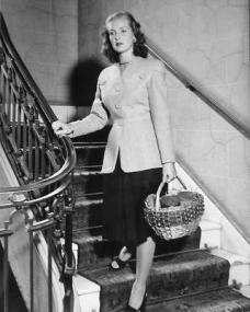 Patricia Roc pauses on the staircase while she carries a wicker basket
