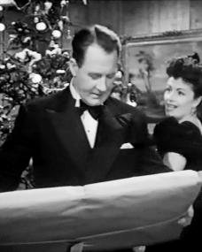Charlie Carrington (Ian Hunter) wonders what his Christmas present is from Bedelia Carrington (Margaret Lockwood) in a photograph from Bedelia (1946) (3)