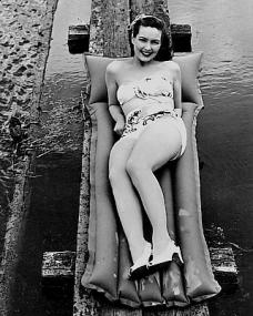 Patricia Roc wears a bikini as she lies on a lilo