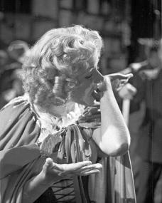 Photograph from Cardboard Cavalier (1949) (20). Nell Gwynne (Margaret Lockwood) licks the remains of a custard pie off her arm