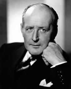 British actor Cecil Parker wears a suit, tie and pocket square