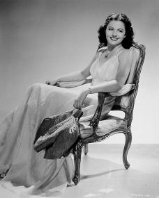 Dance in cotton is Hollywood's fashion slogan straight through the summer.    Margaret Lockwood, now in Paramount's Rulers of the Seas, wears this beguiling, slim dance dress of white cross-bar muslin with a high waistline and narrow shoulder straps.   If the mood permits, Miss Lockwood may wear a brief bolero of bright cerise quilted taffeta, which serves smartly as a youthful wrap.