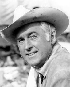 An older Stewart Granger with white hair wears a cowboy hat