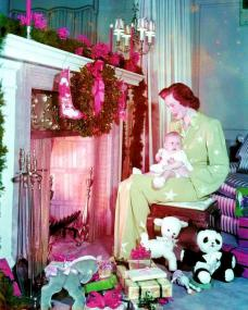 British actress Deborah Kerr is a picture of contentment as she sits in front of her fireplace, cradling a baby  Surrounding the pair are Christmas decorations and presents