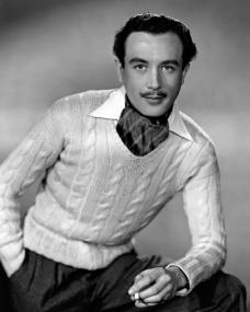 Dennis Price sports a natty moustache, cravat and white jumper, all whilst smoking a cigarette
