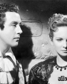 Lady Caroline Lamb (Joan Greenwood) turns away from Lord Byron (Dennis Price) in The Bad Lord Byron (1948).  The couple are seated  in a 19th century padded coach.
