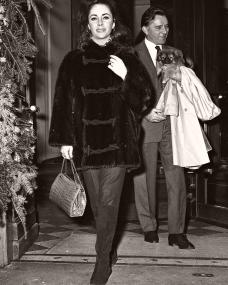 Elizabeth Taylor married Richard Burton in March 1964 and they adopted their daughter Maria that same year. Here, the couple are pictured at the Lancaster Hotel in Paris, where they spent Christmas with their children. Taylor is wearing a $6,000 mink ski jacket from Chombert as she strides past a Christmas tree towards the camera. Burton in the background holds a dog in his arms