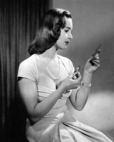 Patricia Roc in a white evening dress and pearl necklace checks the state of her make-up in a compact
