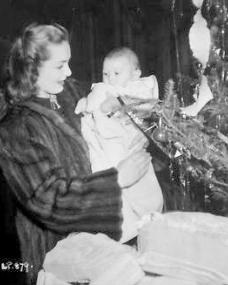 Patricia Roc wears a fur coat as she holds a small baby.  Next to the pair is a rocking horse and Christmas tree.