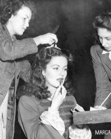 The hairdresser and make-up artist attend to Margaret Lockwood on the set of The Wicked Lady