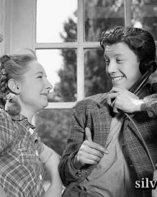 In a phone box, Joe Kirby (Harry Fowler) gives a cheery thumbs up to Mrs Kirby (Vida Hope)