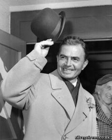 James Mason doffs his hat as he returns home from Hollywood to make a film in England