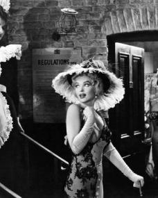 Elsie (Marilyn Monroe) stands at the foot of the stairs and looks back over her shoulder as Maisie Springfield (Jean Kent) opens a nearby door and looks on.  A scene from The Prince and the Showgirl (1957).