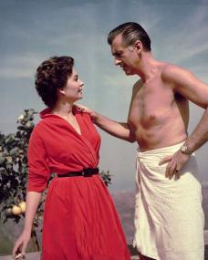Jean Simmons in a red dress with a bare-chested Stewart Granger