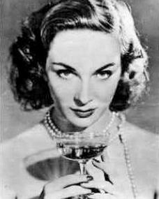 Photo of Joan Greenwood looking out over a glass of champagne