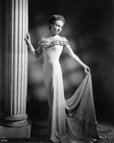 Joan Greenwood holds her dress by a Corinthian column
