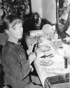 Joan Greenwood looks up from her dressing room table as she prepares for her next performance in the title role of Peter Pan.  Autographed photo reads 'All good wishes, Joan Greenwood'