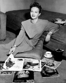 Joan Greenwood reads the magazines of the day while relaxing on a cushion at home