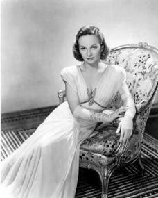 Joan Greenwood in opera gloves rests on an ornate chair.  Try *For the Love of Opera Gloves!* for lovers, collectors and students of this remarkable item of clothing.