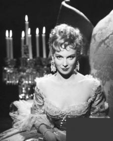 Joan Greenwood in front of a candelabra