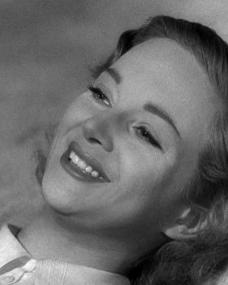 Joan Greenwood as Peggy Macroon smiles as she relaxes contentedly on the beach in Whisky Galore!
