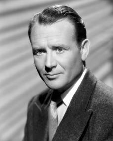 British actor John Mills wears a jacket and tie