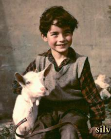 Joe (Jonathan Ashmore), in plaid shirt and grey cardigan, holds his pet goat as they sit outside in A Kid for Two Farthings