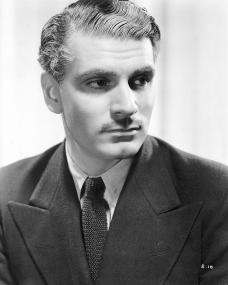 British actor, Laurence Olivier, with a small moustache wears a dark suit and herringbone tie