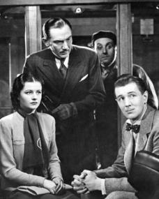 In the train carriage, Dr Hartz (Paul Lucas) questions Signora Doppo (Zelma Vas Dias) as Iris (Margaret Lockwood) and Gilbert (Michael Redgrave) look on