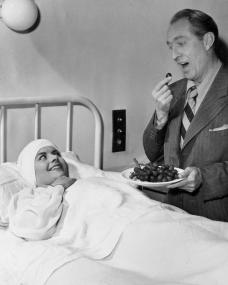 A Day with Margaret Lockwood.   In the morning Margaret Lockwood plays in a scene which is set in a hospital room.   She has just had an eye operation.   While the camera is lined up Director Charles Bennett gives a demonstration of the type of hospital visitor that is a joy to have around.   He brings grapes and eats them all himself.