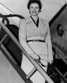 British actress Margaret Lockwood pauses for a publicity shot as she disembarks a BEA flight in the late 1950s/early 1960s.  In her hands she holds a pair of sunglasses and a small bag.