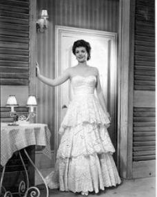 Margaret Lockwood in a white ruffled dress leans against a wood-panelled wall