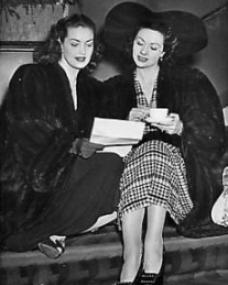 Margaret Lockwood drinks a cup of tea while she looks over the shoulder of fellow 1940s British film star, Patricia Roc