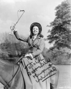 Margaret Lockwood laughs as she raises her riding crop while seated on a horse