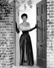 Margaret Lockwood opens her front door on a snowy day while dressed in full-length evening gown and opera gloves