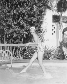 Margaret Lockwood laughs as she dips her toes in the pool while hanging off the diving board