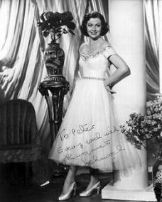 Margaret Lockwood in a white dress and high heels smiles as she stands beside a vase of flowers