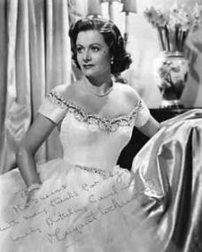 1950s photo of Margaret Lockwood in a white ballgown, with a vase of flowers in the background