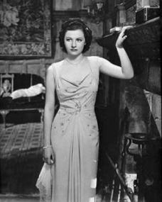 Margaret Lockwood looks pensive as she leans against an ornate chimneypiece
