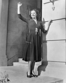 Margaret Lockwood waves cheerfully from the steps of a building