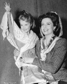 A smiling Margaret Lockwood holds her daughter Julia Lockwood aloft to wave at the crowds