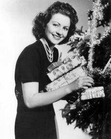 A festive Margaret Lockwood hangs presents on a tinsel-bedecked Christmas tree