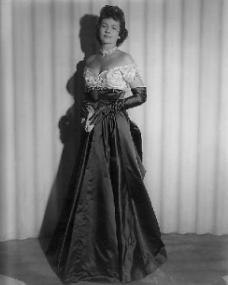Margaret Lockwood wears a full-length evening gown with opera gloves