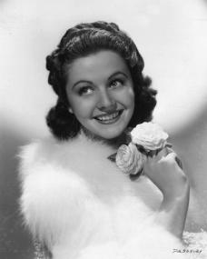 A young Margaret Lockwood holds a pair of white roses